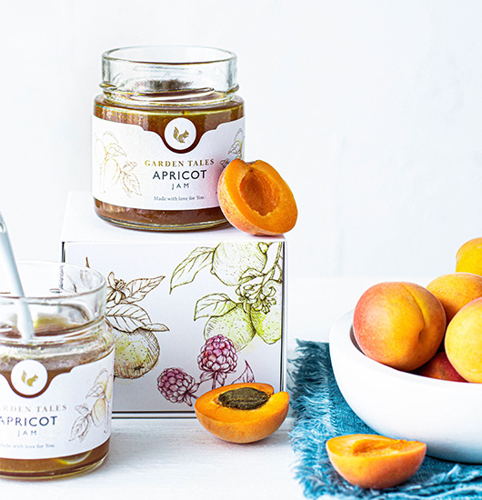 open jar of appricot jam next to appricots